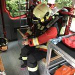 Feuerwehrfrau zieht Atemschutzgerät an