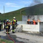 Feuerwehrleute vor brennenden Tonnen