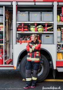 Feuerwehrfrau steht mit verschränkten Armen vor dem Tanklöschfahrzeug