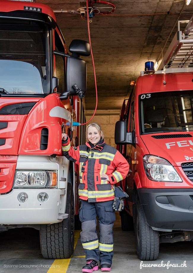 Feuerwehrfrau steht zwischen zwei Feuerwehrfahzeugen