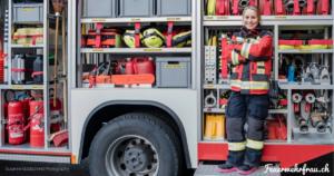 Feuerwehrfrau steht vor dem TLF mit geöffneten Läden