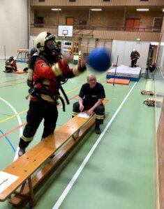 Feuerwehrfrau wirft einen Medizinball an die Wand