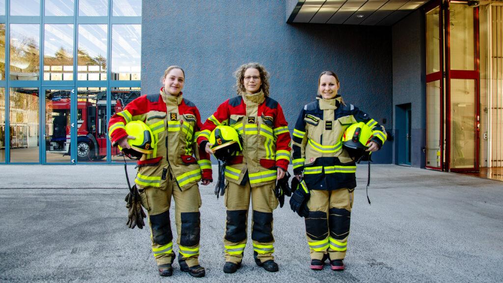 Auf dem Bild sind drei Feuerwehrfrauen der Brandschutzausrüstung zu sehen.